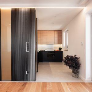Kuchnię odgradza częściowo od pokoju dziennego ażurowa ściana, taka sama jak ta, która znajduje się za sofą w salonie. Projekt Kaza Interior Design. Foto Przemysław Kuciński