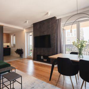 W bezpośrednim sąsiedztwie aneksu kuchennego stanął drewniany stół z czarnymi wygodnymi krzesłami. Projekt Kaza Interior Design. Foto Przemysław Kuciński
