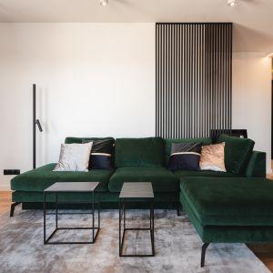 Welurowa sofa w butelkowej zieleni częściowo opiera się o przepierzenie wykonane z pomalowanych na czarno metalowych kształtowników. Projekt Kaza Interior Design. Foto Przemysław Kuciński
