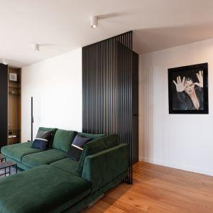 Minimalistycznie urządzone wnętrze ociepla naturalny odcień dębowych desek na podłodze, gruby dywan przy sofie i mięsiste zasłony w uniwersalnym odcieniu szarości. Projekt Kaza Interior Design. Foto Przemysław Kuciński