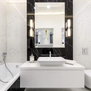 Niewielka łazienka także może być zaaranżowane stylowo. Podstawą są odpowiednio dobrane płytki (na zdjęciu z modnym rysunkiem kamienia) oraz eleganckie wyposażenie. Fot. Moovin Group
