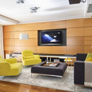 Główną ścianę w salonie wykończono drewnem o ładnym, ciepłym wybarwieniu, które pasuje do żółtych foteli i nieco ciemniejszej szarej kanapy. Projekt: Aleksandra Węgiełek. Fot. Mariusz Purta