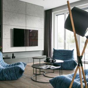 Ścianę za telewizorem wykończono betonem i ciemną szarą farbą. Surowy klimat łagodzi nieco dębowa podłoga w delikatnym brązie. Projekt: Joanna Zabłocka. Fot. Zawrotniak-Kucharska