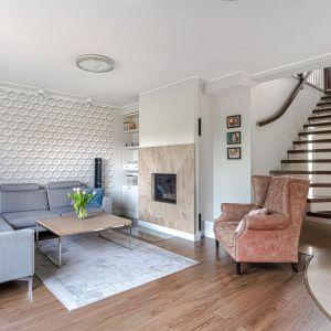 Ścianę za kanapą zdobi ładna tapeta, na obudowie kominka pojawił się zaś naturalny kamień. Projekt Beata Ignasiak. Fot. Wojciech Łowicki