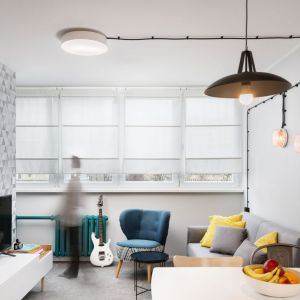 Mały salon urządzono w jasnych kolorach. Charakteru dodaje mu ściana za telewizorem wykończona tapaetą. Projekt i zdjęcia: Kasia Kokot/Pracownia Inside