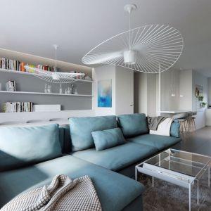 Ścianę za kanapą wykorzystano bardzo praktycznie na liczne szafki i półki. Projekt i zdjęcia: Naboo Studio
