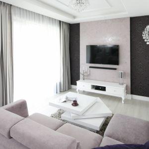 Ścianę z telewizorem wykończono elegancką tapetą w kolorze pasującym do tapicerki kanapy. Po obu stronach zdobią ją ciemniejsze pasy tapety. Projekt: Katarzyna Mikulska-Sękalska. Fot. Bartosz Jarosz