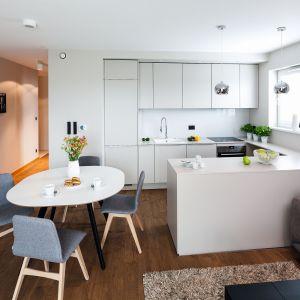 Ta prosta i funkcjonalna kuchnia w kształcie litery U, z podręcznym półwyspem i białymi frontami do bardzo dobra propozycja do otwartego wnętrza. Projekt Katarzyna Uszok. Fot. Bartosz Jarosz