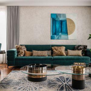 Sofa w kolorze butelkowej zieleni wyznacza przestrzeń do wypoczynku. Projekt Safranow. foto. Fotomohito