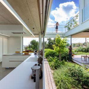 Kuchnia z prostą minimalistyczną zabudowa tworzy jedną całość z ogrodem. Projekt i zdjęcia: Christos Pavlou Architecture