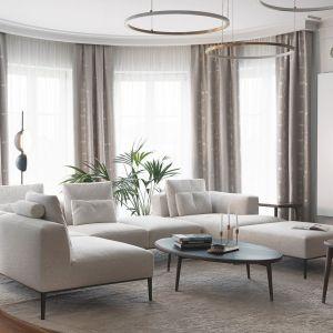Okrągły dywan w beżowym kolorze świetnie pasuje do jasnej, stylowej aranżacji salonu. Projekt i zdjęcia: JT Group