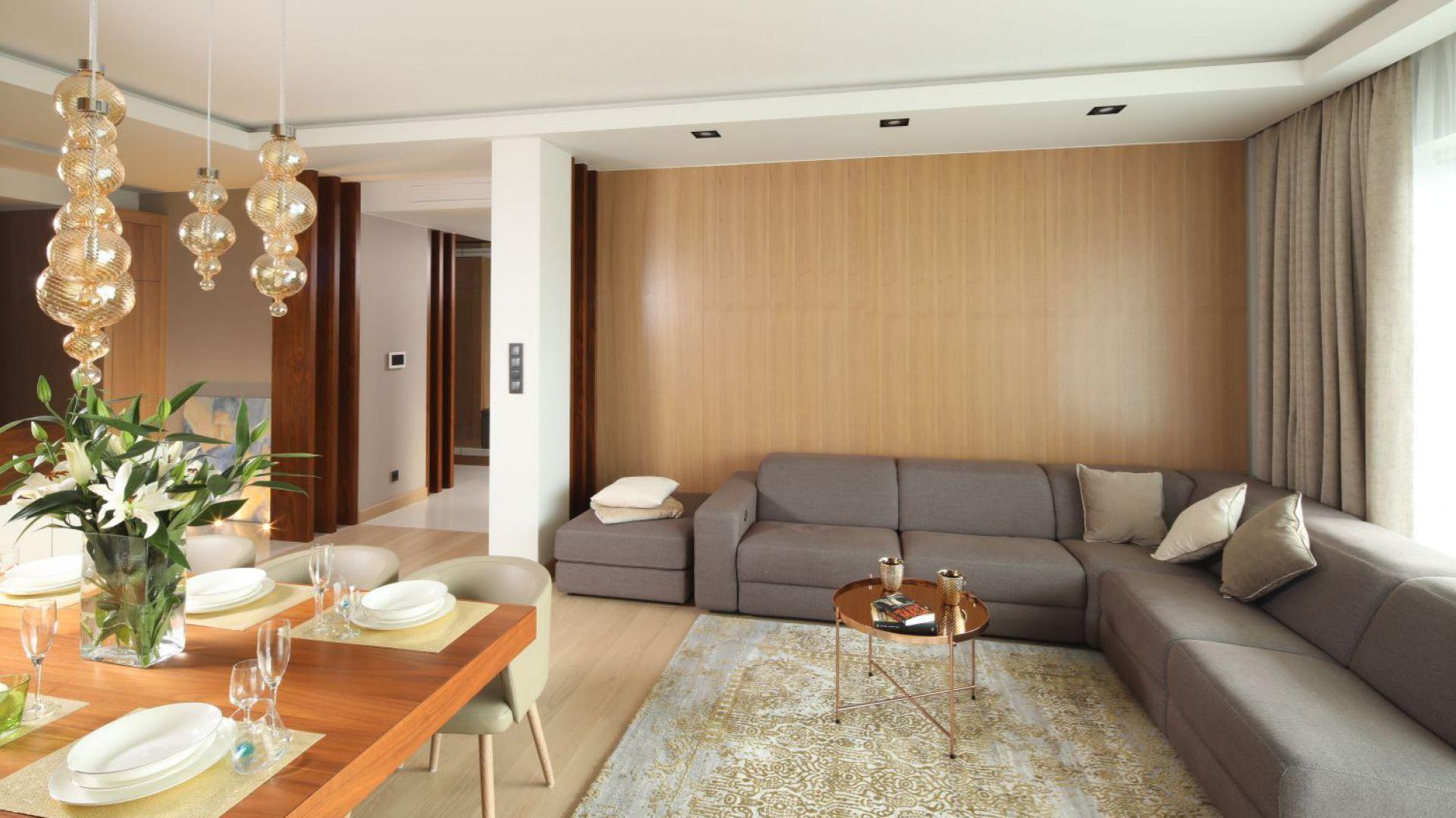 Dywan w subtelny złoty wzór pięknie dopełnia przytulną aranżację salonu. Projekt: Laura Sulzik. Fot. Bartosz Jarosz