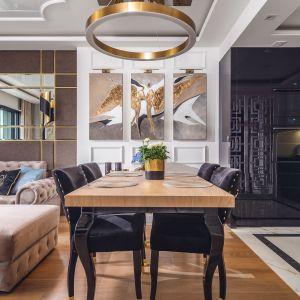 W części dziennej znajduje się stół z tapicerowanymi krzesłami, sofa oraz zabudowa RTV z naturalnym onyksem. Projekt: Agnieszka Hajdas-Obajtek. Fot. Wojciech Kic