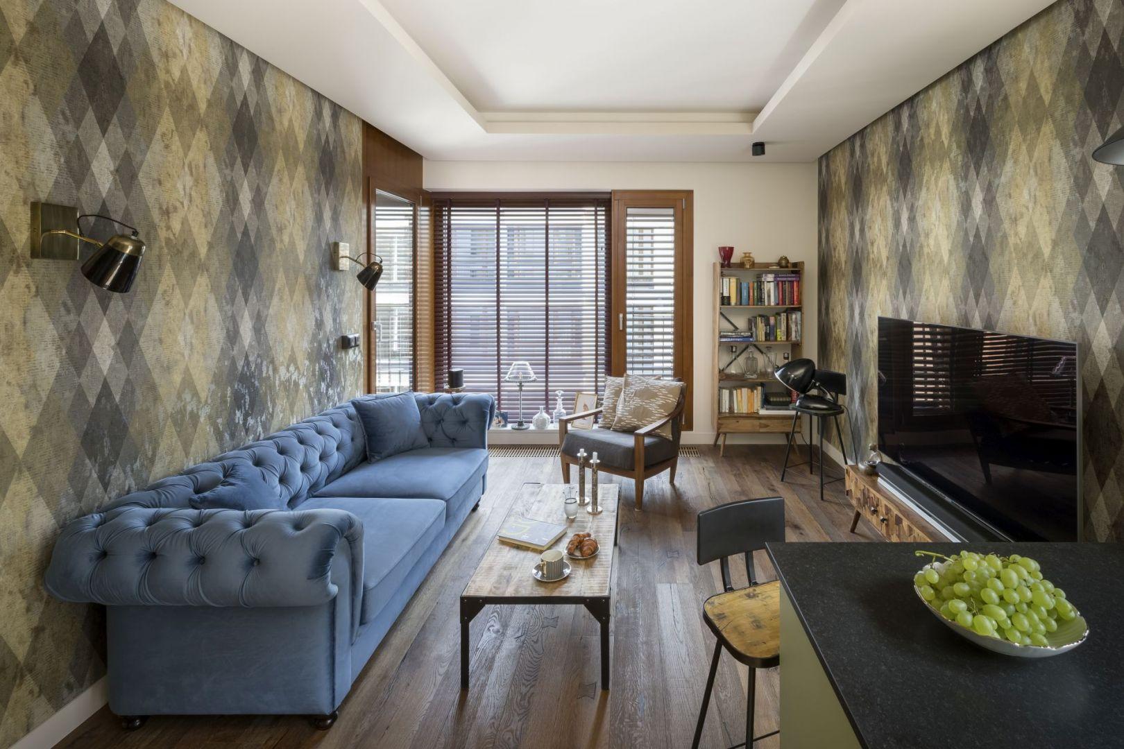 Głównym akcentem dekoracyjnym salonu są ozdobne tapety. Pierwotnie miały być w odcieniu niebieskim, ale projektantka przekonała właściciela do zieleni. Projekt: Magdalena Miśkiewicz. Fot. Łukasz Zandecki
