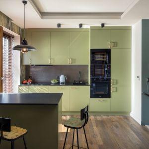 Kolor prostej, nowoczesnej zabudowy nawiązuje do ścian w części dziennej i nadaje ton przestrzeni. Dzięki temu kuchnia nie jest zwyczajna – jej kolor i styl tworzą eklektyczną całość. Projekt: Magdalena Miśkiewicz. Fot. Łukasz Zandecki