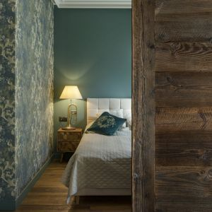 Przesuwnymi drzwiami z litego drewna, które bardzo dobrze komponują się z podłogą z postarzanych, szczotkowanych desek, skrywają przestrzeń sypialni. Projekt: Magdalena Miśkiewicz. Fot. Łukasz Zandecki