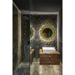 Na podłodze i na ścianie przy umywalce pojawiły się płytki w stylu retro. Na ich tle pięknie wyeksponowano lustro w oryginalnej ramie, wykonanej na zamówienie z bursztynu. Projekt: Magdalena Miśkiewicz. Fot. Łukasz Zandecki