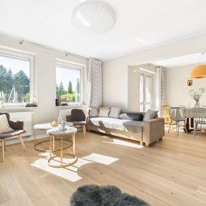 Przestronny salon w domu połączony z jadalnią - kolorowe drewniane krzesła to strzał w dziesiątkę! Projekt Małgorzata Bacik, Andrzej Bacik. Fot. Jeremiasz Nowak