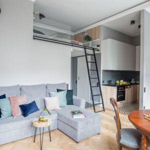 Mieszkanie ma naprawdę mały metraż, dlatego kuchnię zaaranżowano w formie aneksu, a częścią salonu stała się też niewielka jadalnia. Projekt Monika Pniewska. Fot. Marta Behling  Pion Poziom.