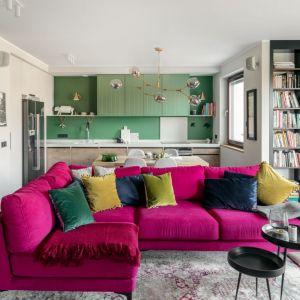 Narożnik w mocnym, różowy kolorze zajmuje główne miejsce w salonie. Projekt: Finchstudio. Fot. Aleksandra Dermont Ayuko Studio