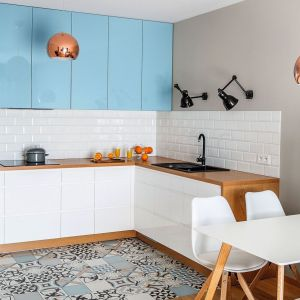 Szafki górne w błękitnym kolorze doskonale pasują do białych elementów i dodatków o barwie miedzi. Projekt i zdjęcia: Decoroom. Fot. PionPoziom