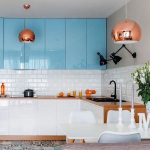 Szafki górne w błękitnym kolorze pięknie ożywiają jasną przestrzeń kuhcni. Projekt Decoroom. Fot. Pion Poziom.
