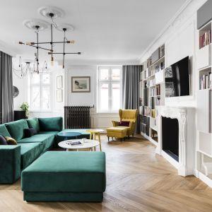Charakteru przestrzeni salonu dodają śmiałe kolory. To  butelkowa zieleń oraz intensywna żółć, które wprowadzono do projektu w postaci narożnej kanapy i stylowego fotela. Projekt: Anna Maria Sokołowska. Fot. Foto&Mohito