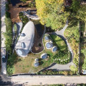Wykonany ze zbrojonego betonu budynek wyłania się z ziemi pośród dużych połaci trawy i terenów dookoła pokrytych niczym dywanami. Kompozycja architektoniczna rozwija się od zewnątrz do wewnątrz, gdzie ogromne okna nawiązują nierozerwalny związek z naturą.