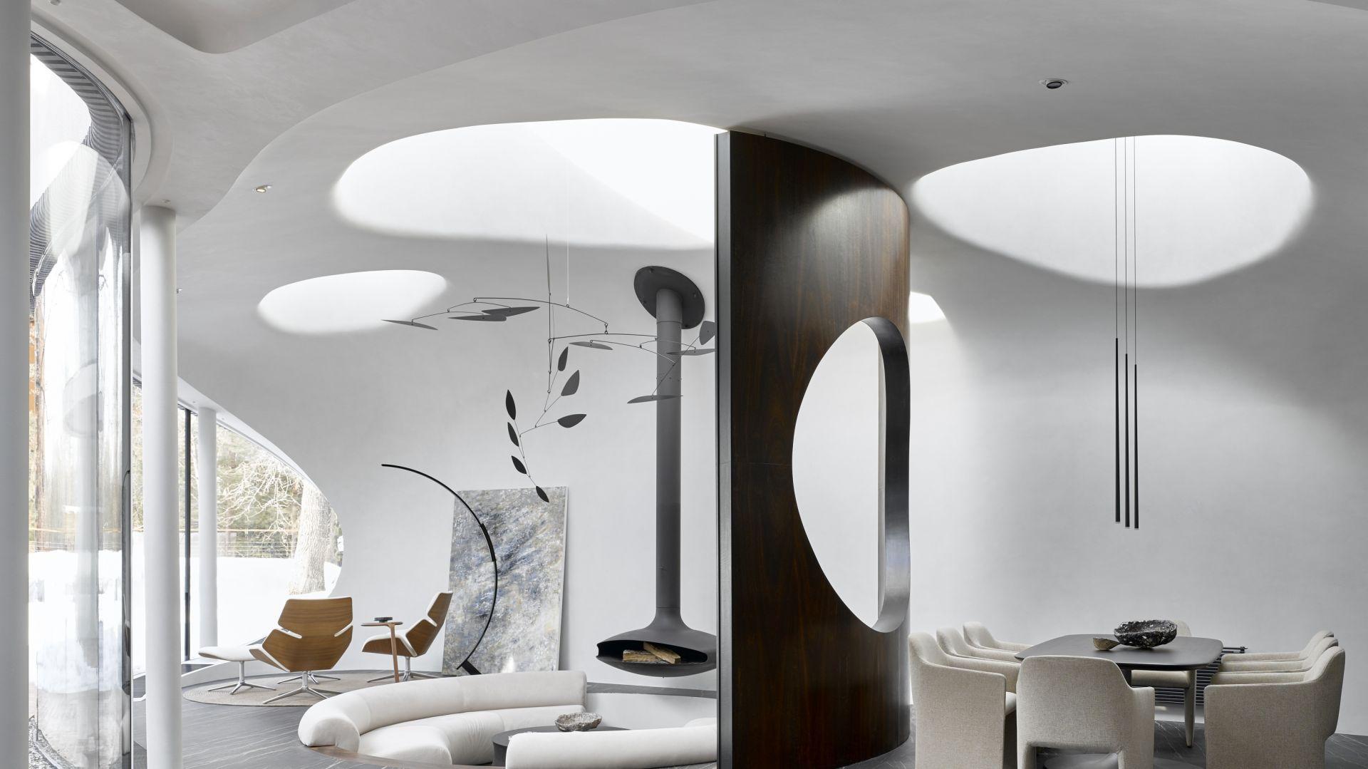 Kompozycja architektoniczna rozwija się od zewnątrz do wewnątrz, gdzie ogromne okna podkreślają nierozerwalny związek projektu z naturą.