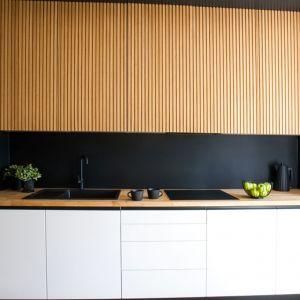 Ścianę nad kuchennym blatem zdobi czarne, matowe, piaskowane szkło. Projekt: Sandra Maculewicz. Fot. Łukasz Pepol