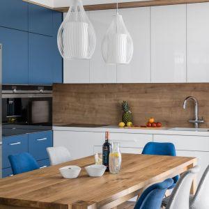 Ścianę nad blatem w kuchni zdobi drewno, które w połączeniu z bielą i kolorem niebieskim, prezentuje się doskonale. Projekt: Studio Projekt. Fot. Fotomohito