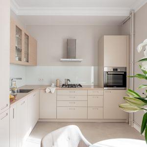 Ścianę nad blatem w kuchni wykończono jasnym szkłem. Projekt i zdjęcia: Finch Studio