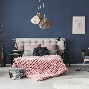 Ciemny kolor farby na ścianie za łóżkiem to dobry pomysł - w takim wnętrzu odpoczniemy lepiej. Zgaszony granat to supermodny pomysł! Fot. Dekoral