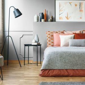 Matowa szara ściana za łóżkiem w sypialni. W duecie z jesiennymi odcieniami czerwieni prezentuje się znakomicie. Fot. Tikkurila