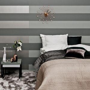Pomysł dla odważnych - ściana za łóżkiem w sypialni pomalowana w poziome pasy w różnych odcieniach szarości. Fot. Tikkurila