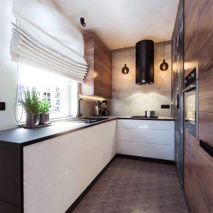 Kolorystyka w kuchni jest kontynuacją przestrzeni salonowej, jedynie odcień drewna na meblach mamy nieco ciemniejszy. Projekt i wizualizacje: Monika Staniec, Interior Design
