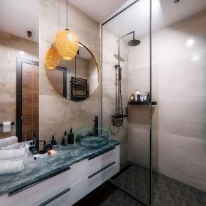 W łazience znajduje się prysznic z odpływem podłogowym, umywalka stojąca na blacie szafki, toaleta podwieszana i mnóstwo miejsca do przechowywania. Projekt i wizualizacje: Monika Staniec, Interior Design