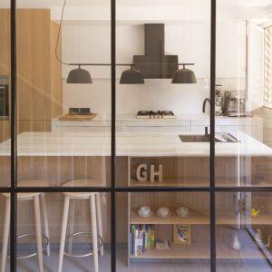 W części dziennej postawiono na przeszklenia, które funkcjonalnie oddzielają od siebie salon i jadalnię z kuchnią, a jednocześnie nie zmniejszają powierzchni. Projekt i zdjęcia: Gokostudio Architecture (Hiszpania)