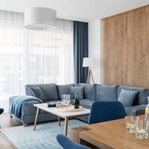 Niebieskie zasłony idealnie pasują do tapicerki kanapy, foteli oraz do dywanu. Projekt: Studio Projekt. Fot. Fotomohito