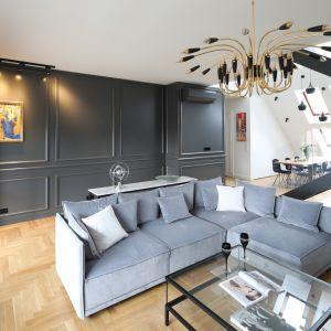 Złoty majestatyczny żyrandol podkreśla neoklasyczny charakter aranżacji salonu. Projekt Katarzyna Mikulska-Sękalska