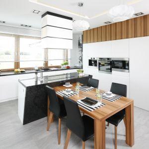 Aby bieli kuchennych szafek dodać nieco charakteru, często ociepla się je drewnem.  Projekt Katarzyna Mikulska-Sękalska. Fot. Bartosz Jarosz