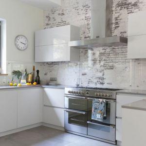 Nowoczesna biała kuchnia z frontami w połysku i ciekawie rozwiązaną ścianą między szafkami (szkło+tapeta). Projekt Małgorzata Denst. Fot. Marta Behling/Pion Poziom