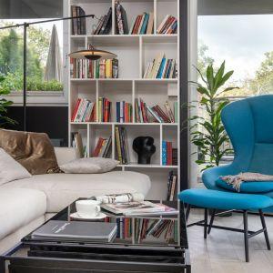 Niebieski fotel z podnóżkiem zachęca do wypoczynku. Projekt Mikołajska Studio