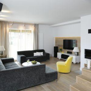 Żółty fotel ożywia przestrzeń salonu. Projekt Małgorzata Galewska
