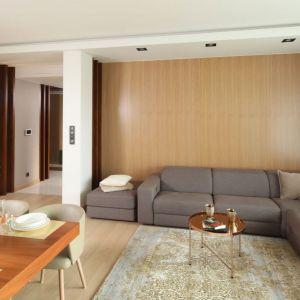 Ciepłe drewno w miodowym wybarwieniu zdobi ścianę za kanapą. Projekt Laura Sulzik