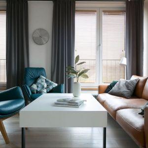 Niebieskie fotele i wygodna, pomarańczowa kanapa przełamują stonowaną paletę szarości i dodają salonowi przytulności. Projekt: MIKOŁAJSKAstudio. Fot. Jakub Dziedzic (Wnętrza Kraków)