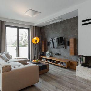 Nowocześnie urządzony salon ocieplają drewniana podłoga oraz meble. Projekt i zdjęcia: Agnieszka Cupryś-Wilk z pracowni Archissima,