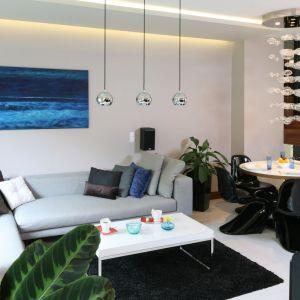 Przytulny salon urządzony został w jasnych szarościach, które ożywiają turkusy i granat. Projekt: Chantal Springer. Fot. Bartosz Jarosz