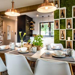 W otwartej części dziennej tego domu zwraca uwagę zastosowanie naturalnych materiałów, takich jak ściana z mchu w jadalni. Projekt Małgorzata Szpak. Fot. Lukas Patecki