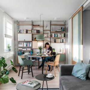 Niewielki salon z jadalnią urządzony z użyciem naturalnych materiałów, kolorów i żywych roślin. Projekt Raca Architekci. Fot. Fotomohito